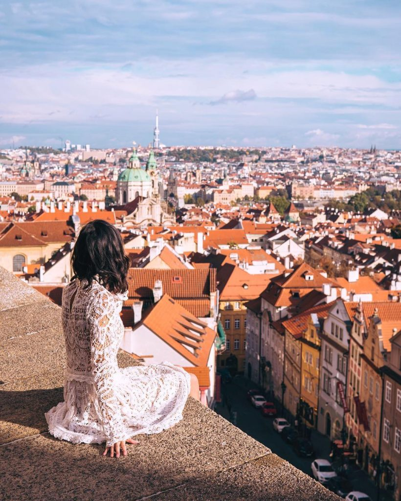 girl on ledge of balcony in the Back of Schwarzenbersky Palace Prague - witandfolly.co