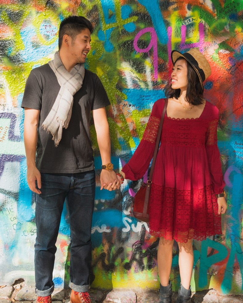 photo of couple in front of the lennon wall artwork in prague