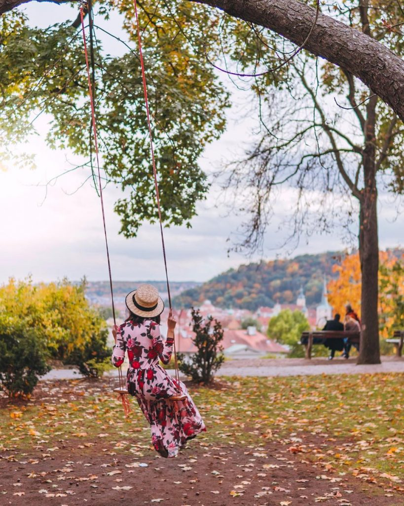 girl on a swing hanging from a tree with a view of prague