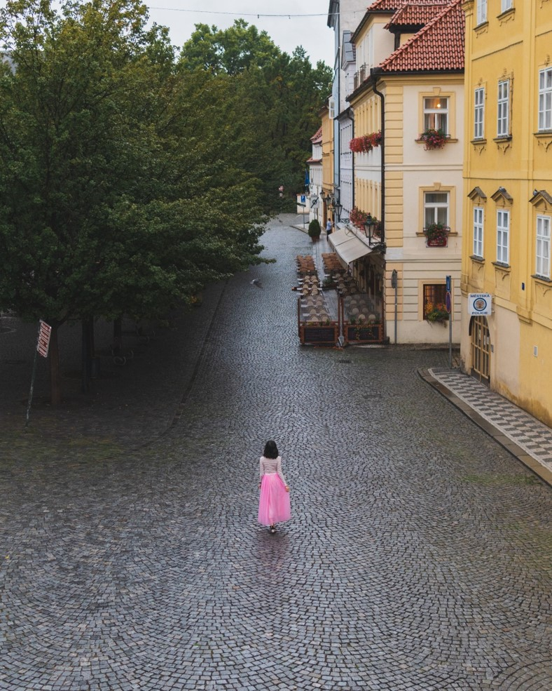 girl wearing a pink dress in the middle of empty cobblestone street