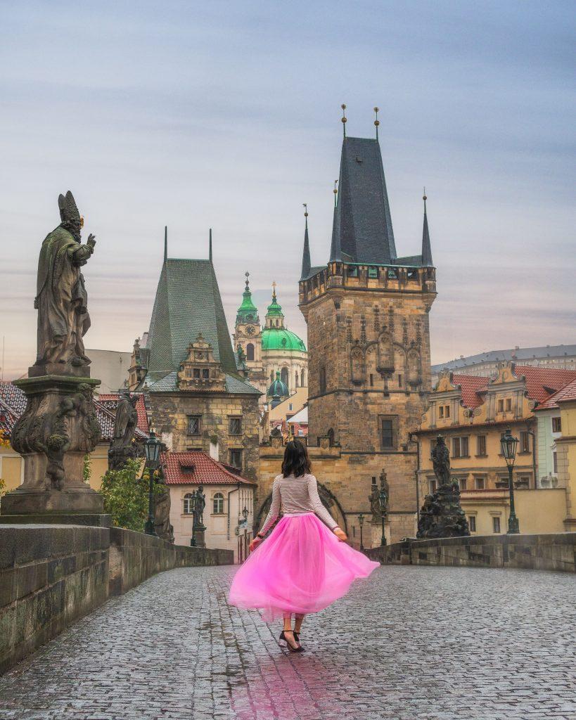 girl in pink dress twirling on charles bridge in prague