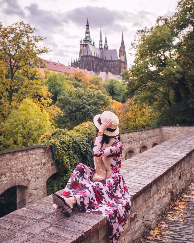 photo of girl on ledge with a view of prague castle
