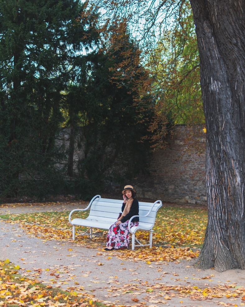 girl sitting on bench with fall colors and trees