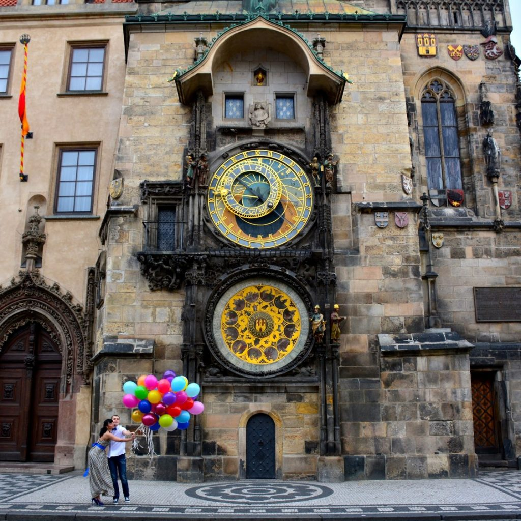 couple in front of astronomical clock in prague
