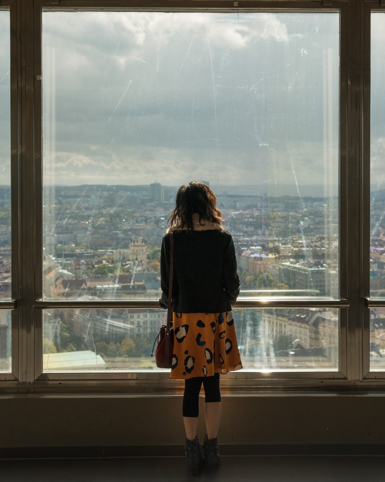 girl looking out the window on top of zizkov tower