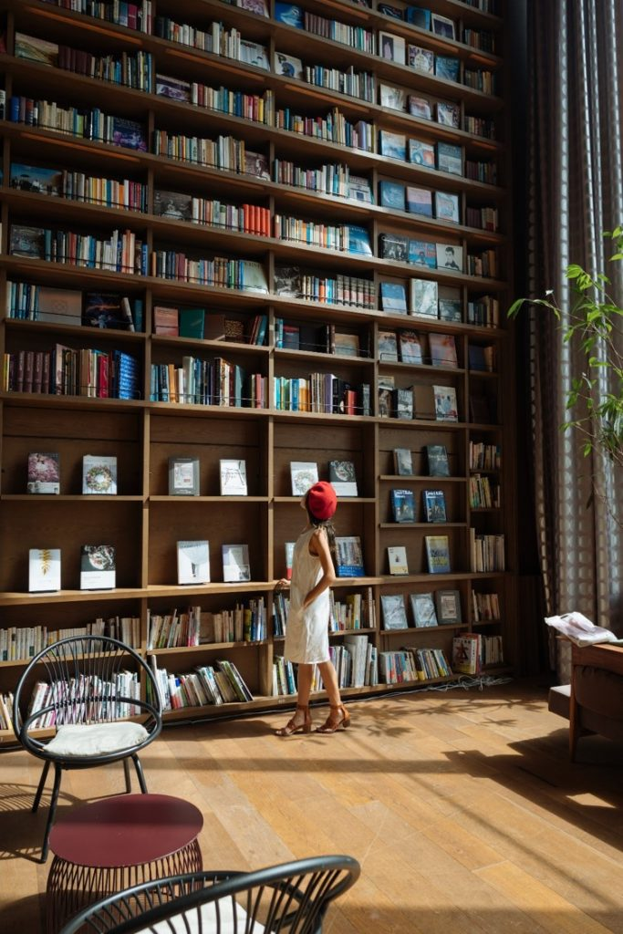 image of a girl standing and looking up at a bookshelf full of books
