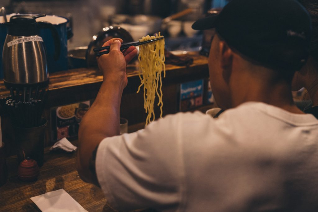 image of a person picking up noodles with chopsticks