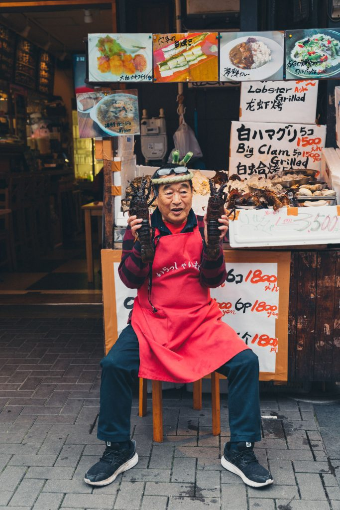 image of vendor at japanese market holding up lobster in each hand