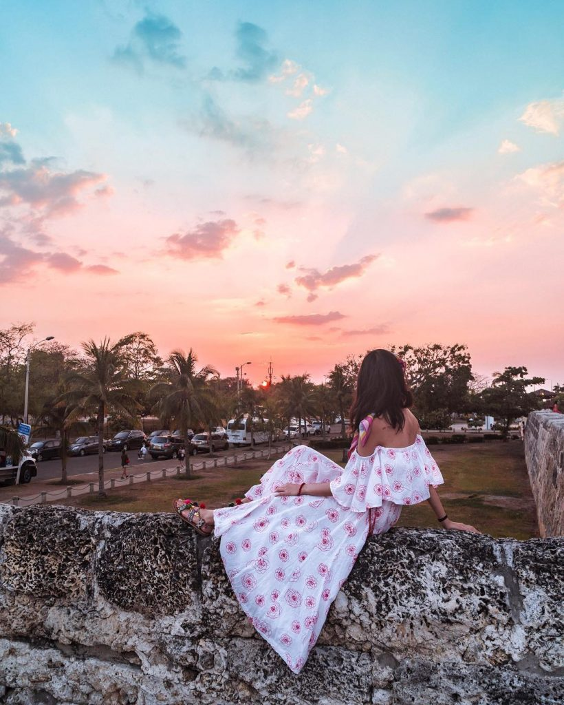 Sitting on the wall in the Old Walled City in Cartagena - witandfolly.co