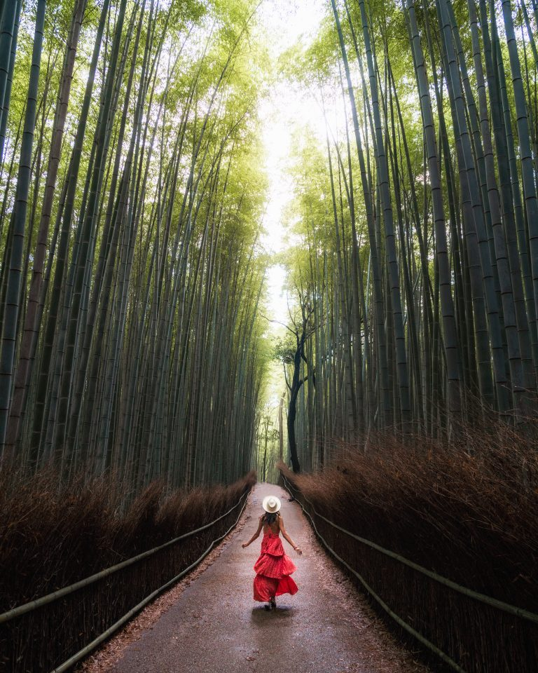 woman in red dress twirling in arashiyama bamboo forest in kyoto