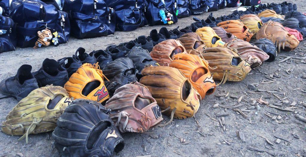 line of baseball gloves on the ground