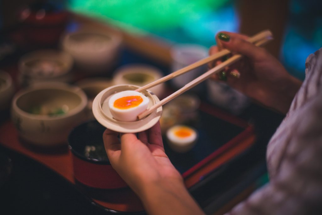 picture of person holding eggs with chopsticks in japan
