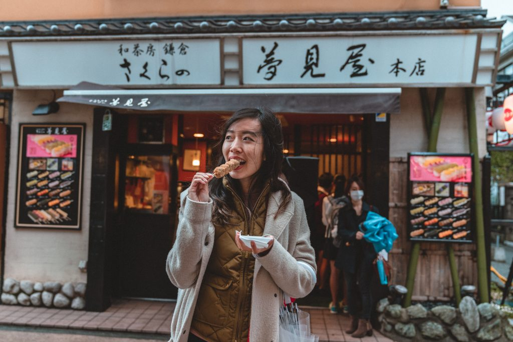 Girl eating mochi in front of Japanese store