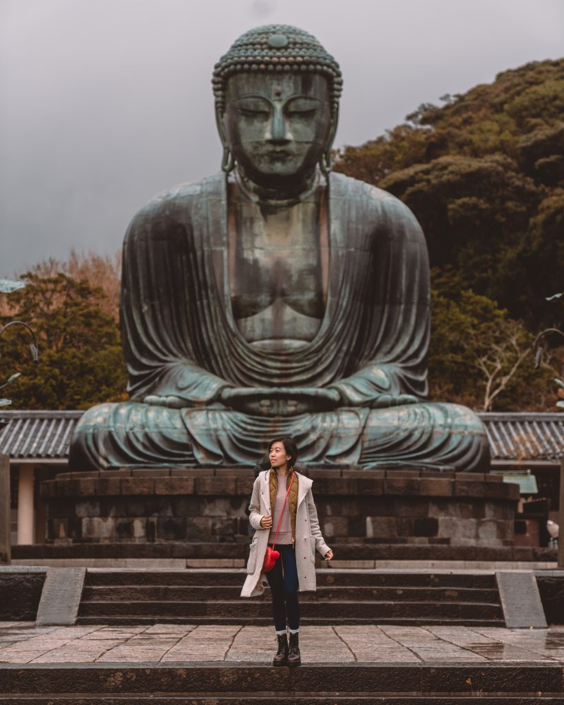 girl standing in front of large buddha statute
