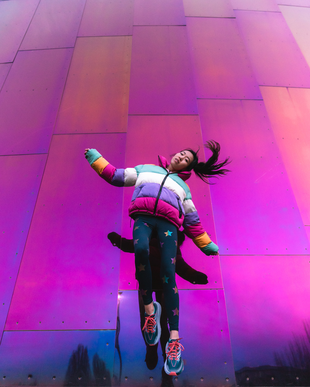 Girl jumping up in front of colorful pink wall