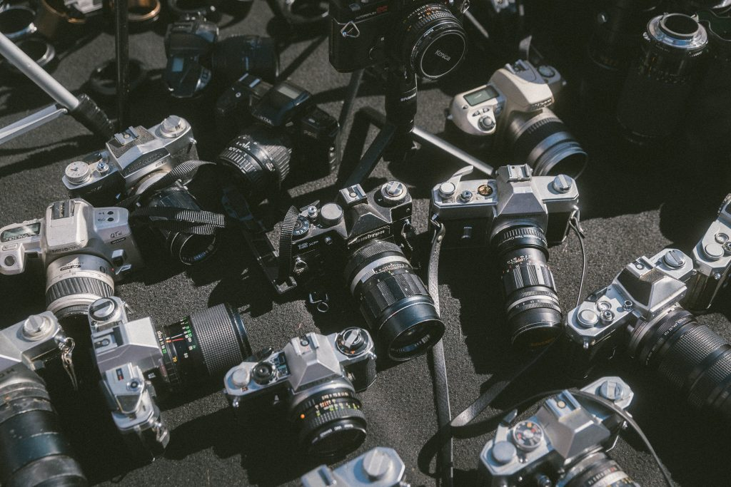 photo of a bunch of vintage cameras on the ground