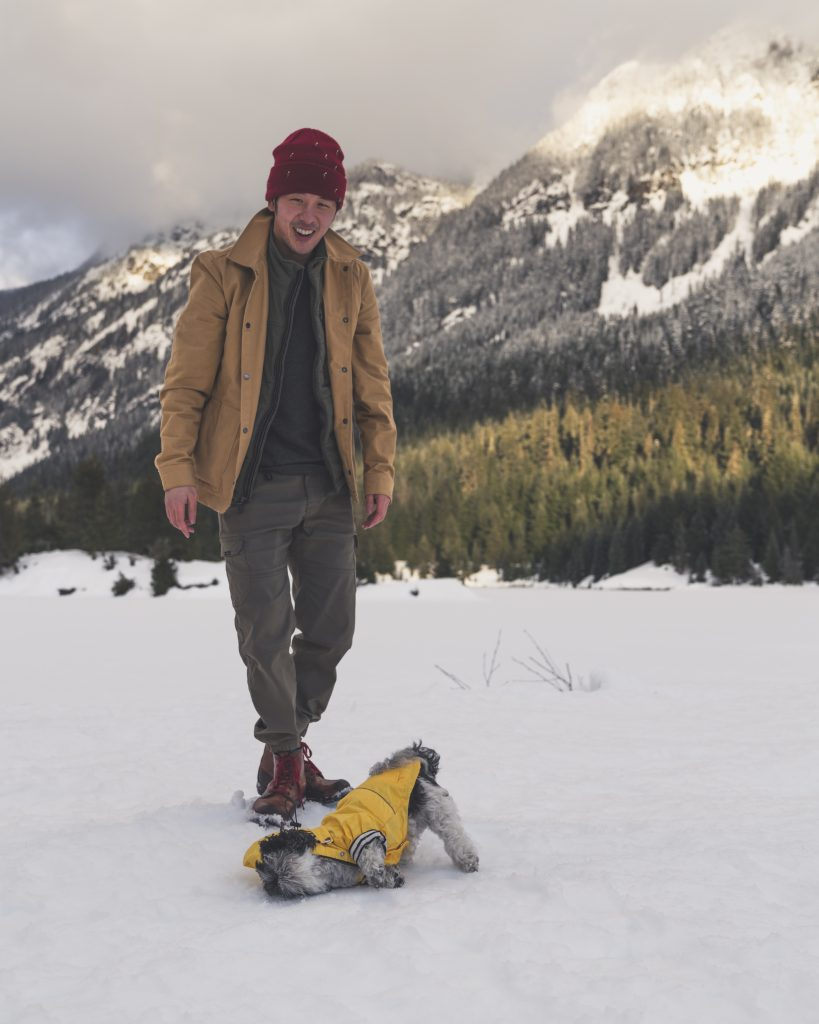 image of a guy smiling and his shih tzu dog in a winter scene. The shih tzu is in a yellow rain jacket rolling in the snow and the guy is smiling because its funny.