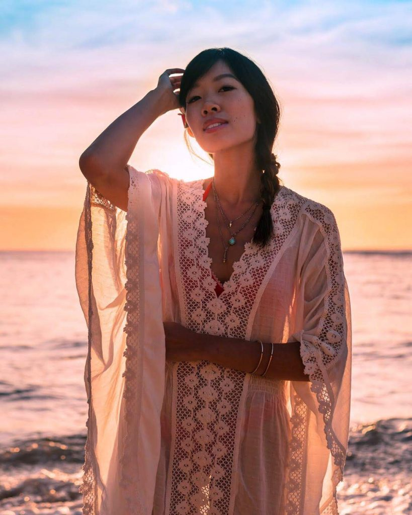 image of a girl in flowing white dress in the morning glow of the sunrise in hawaii. The girl has her right hand touching her head and is facing the camera.