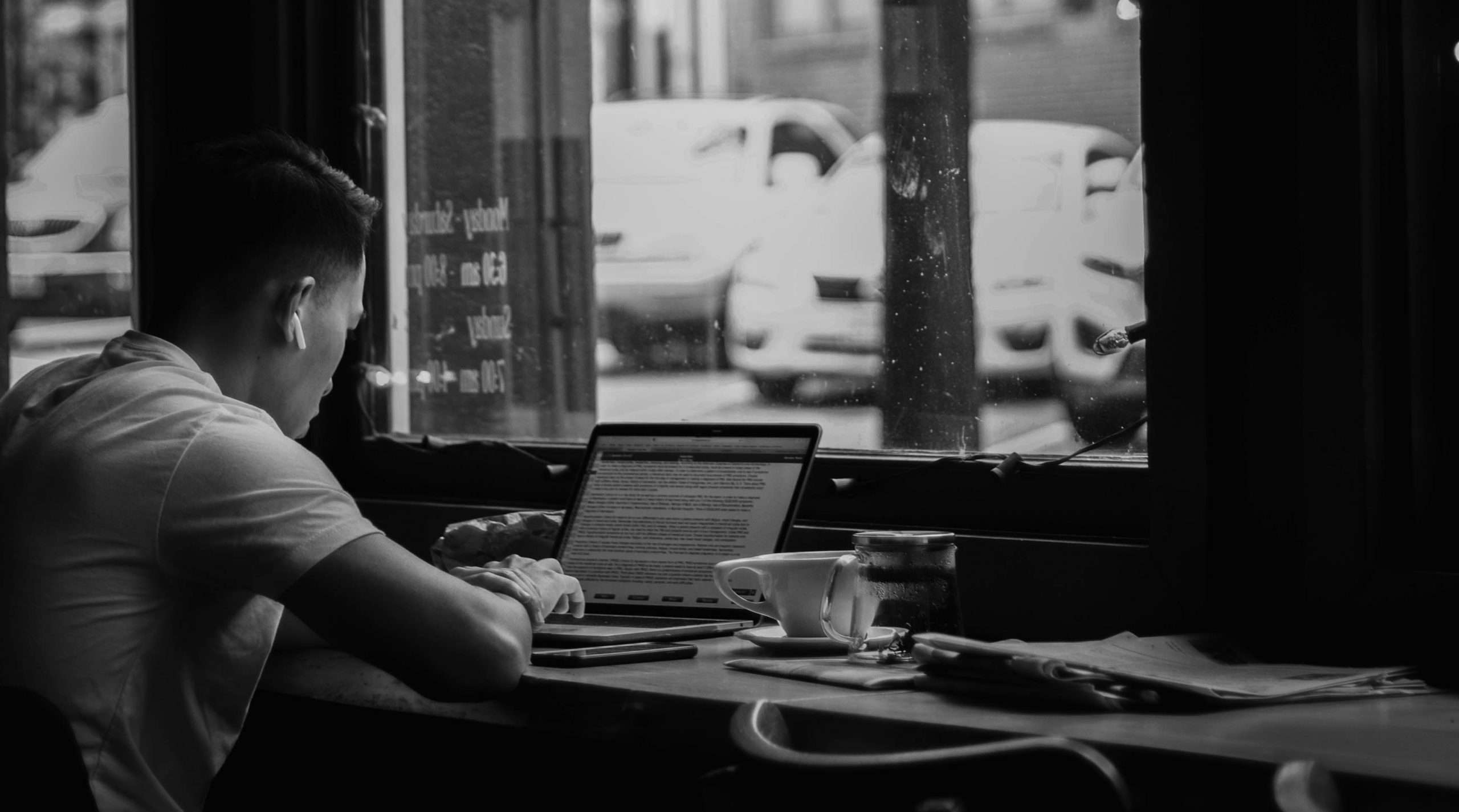 black and white image of person using laptop