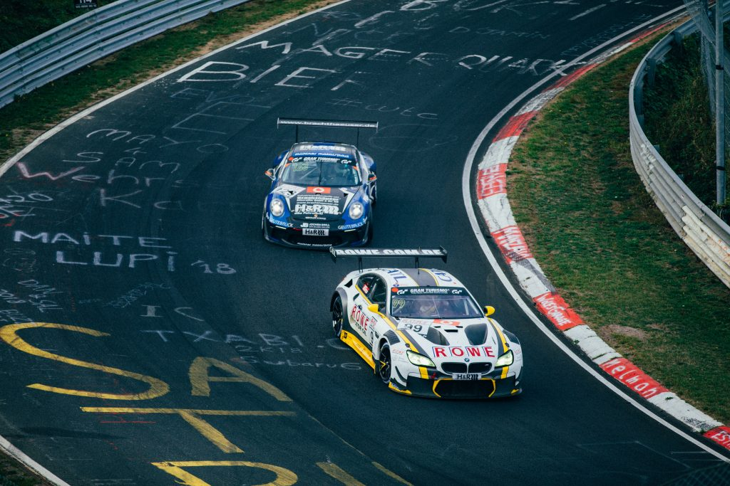 photo of two cars racing on a race track