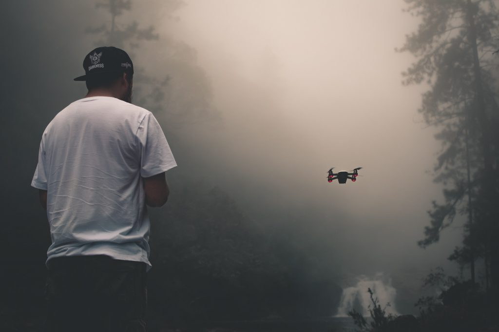 man flying a drone in cloudy conditions