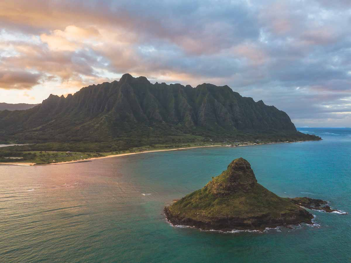 drone shot image of an island in the ocean in front of a mountain range