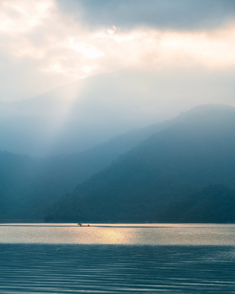 image of sun shining through the clouds at sun moon lake