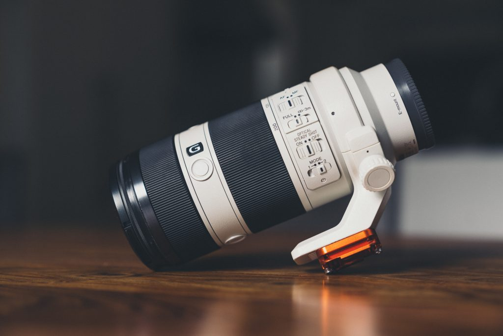 image of zoom lens on wood table with dark background