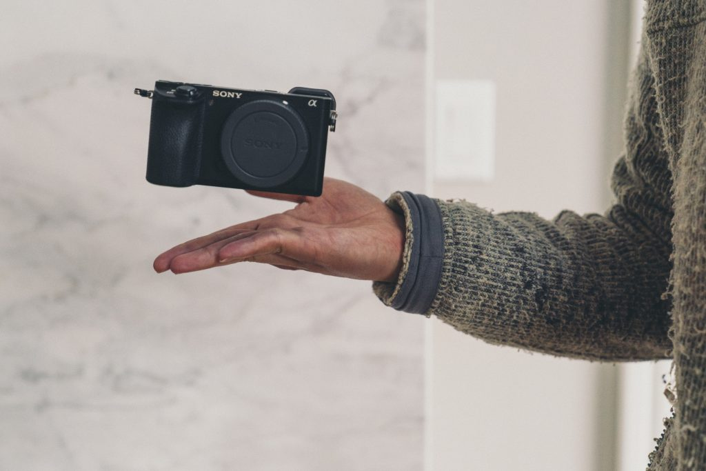 image of camera being thrown up against white background