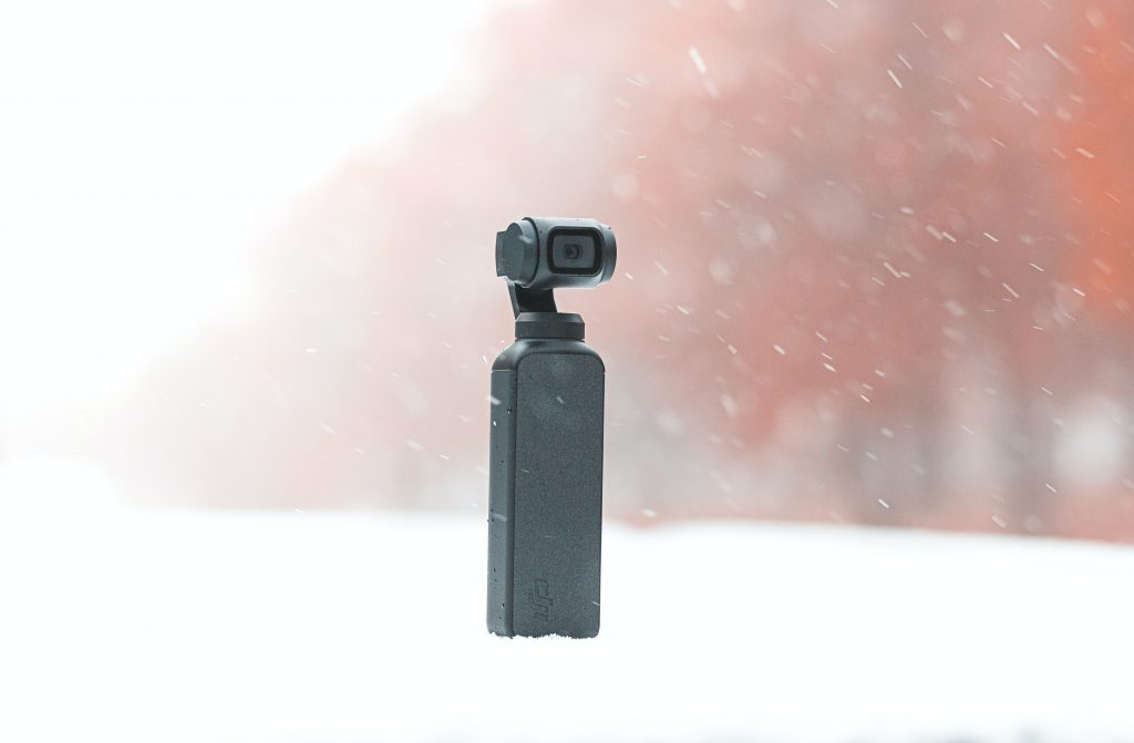 image of small black compact camera in the snow