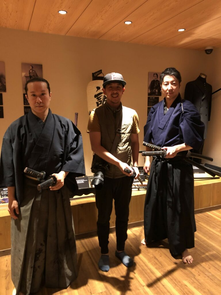 person standing between two people dressed as samurai. the person in the middle is smiling so it seems like its for fun