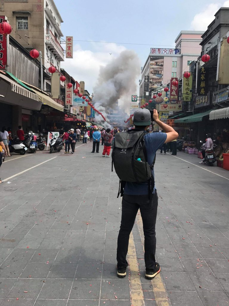 image of person with backpack shooting a camera with smoke in the background