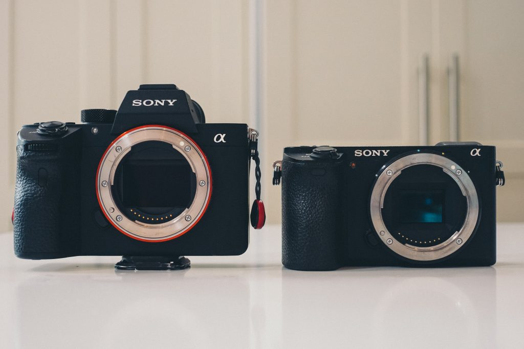 image of two black cameras side by size to show the different sensor size
