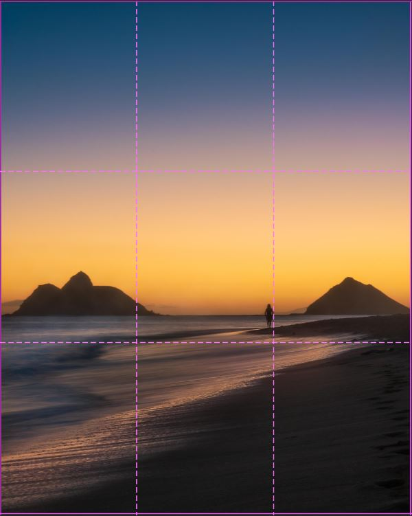 image of lanikai beach at sunrise with a person standing on the beach and two islands in the background. sky is glowing orange with rule of third grid overlayed.