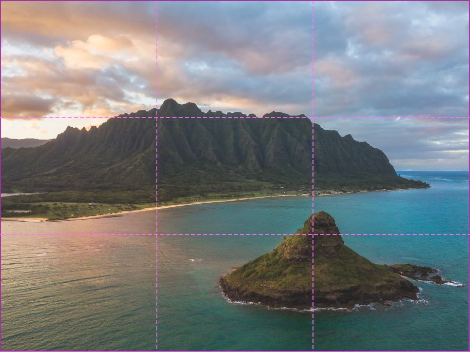 image of an island in the ocean with a mountain range in the back at sunset with the rule of third grid overlayed