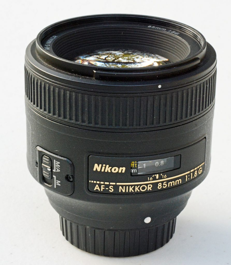 nikon 85mm f.18 in front of white background