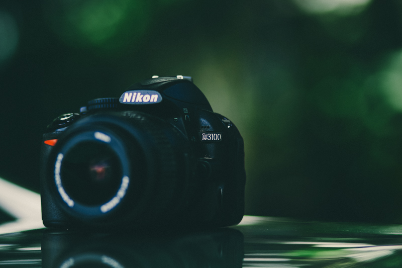 image of nikon d3100 against a green background