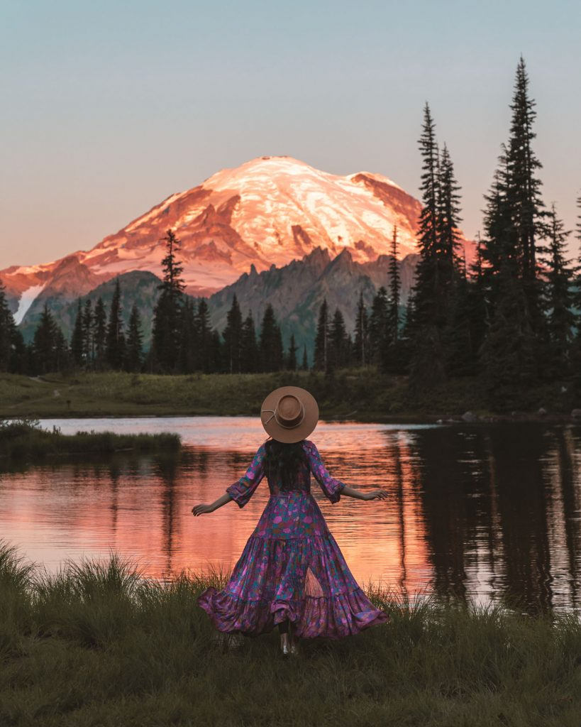 girl in flowy dress in front of lake reflection of mount rainier with orange glow