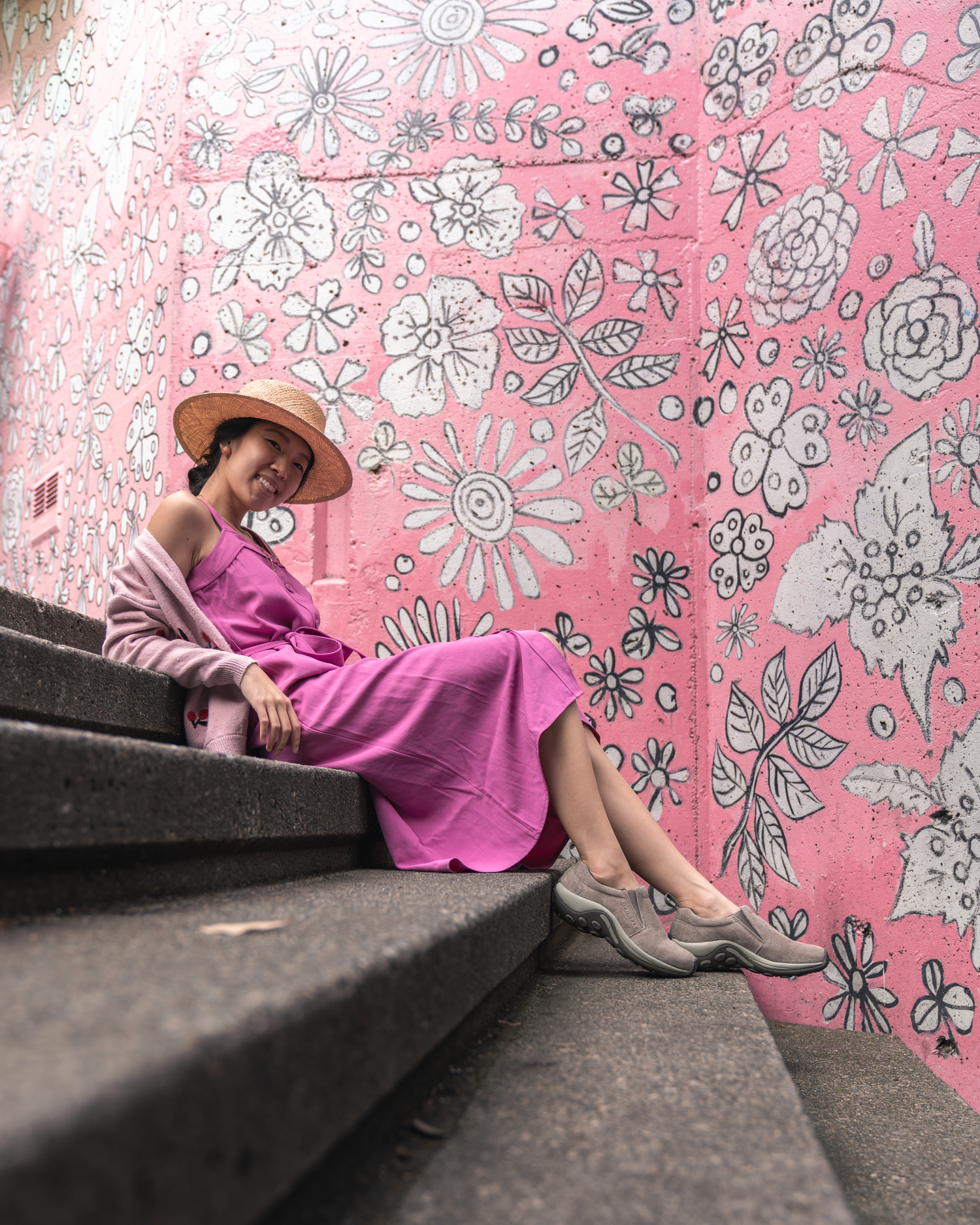 Girl sitting on stairs in front of pink mural