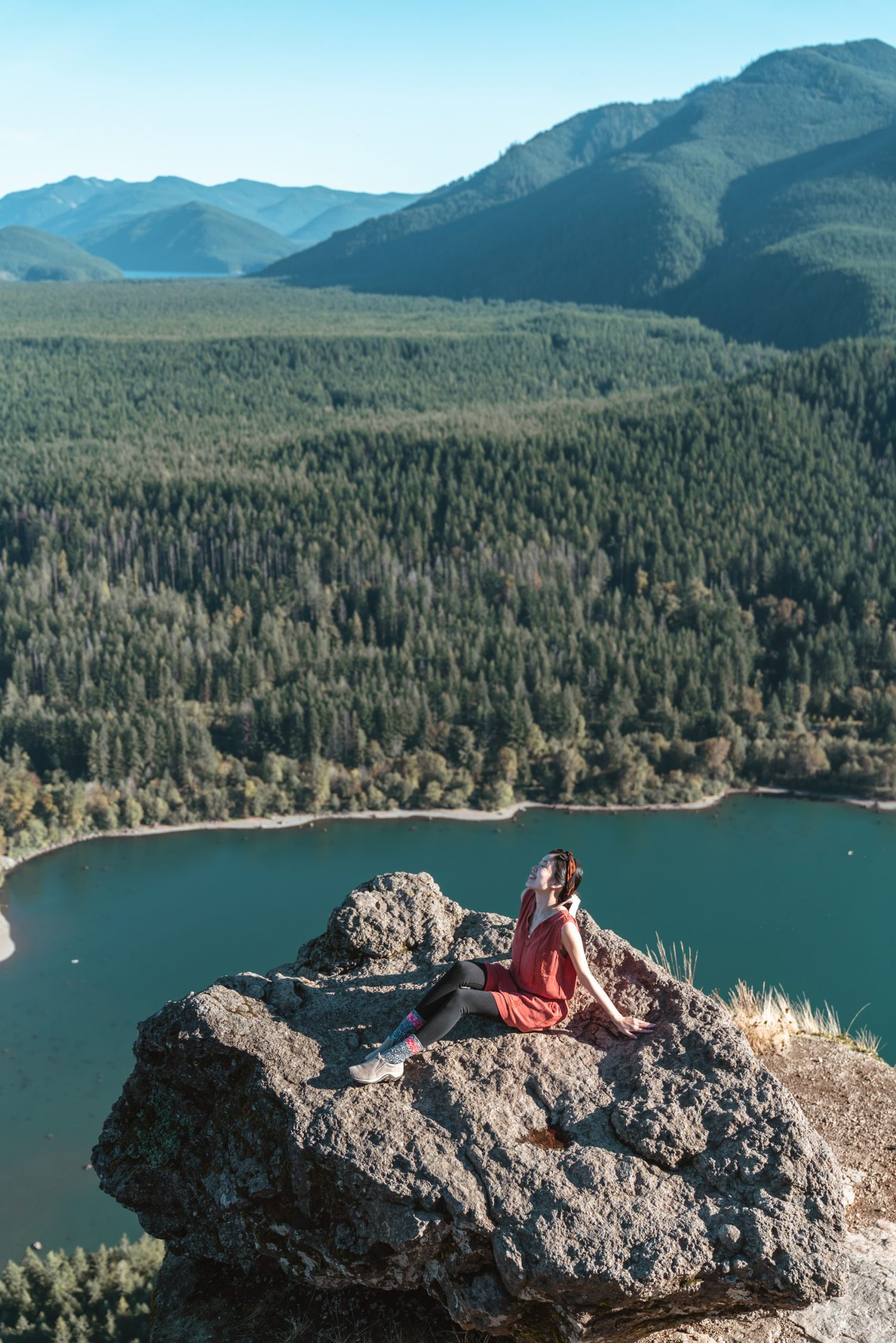 Girl sitting on top of large rock overlooking lake at Rattlesnake Ledge