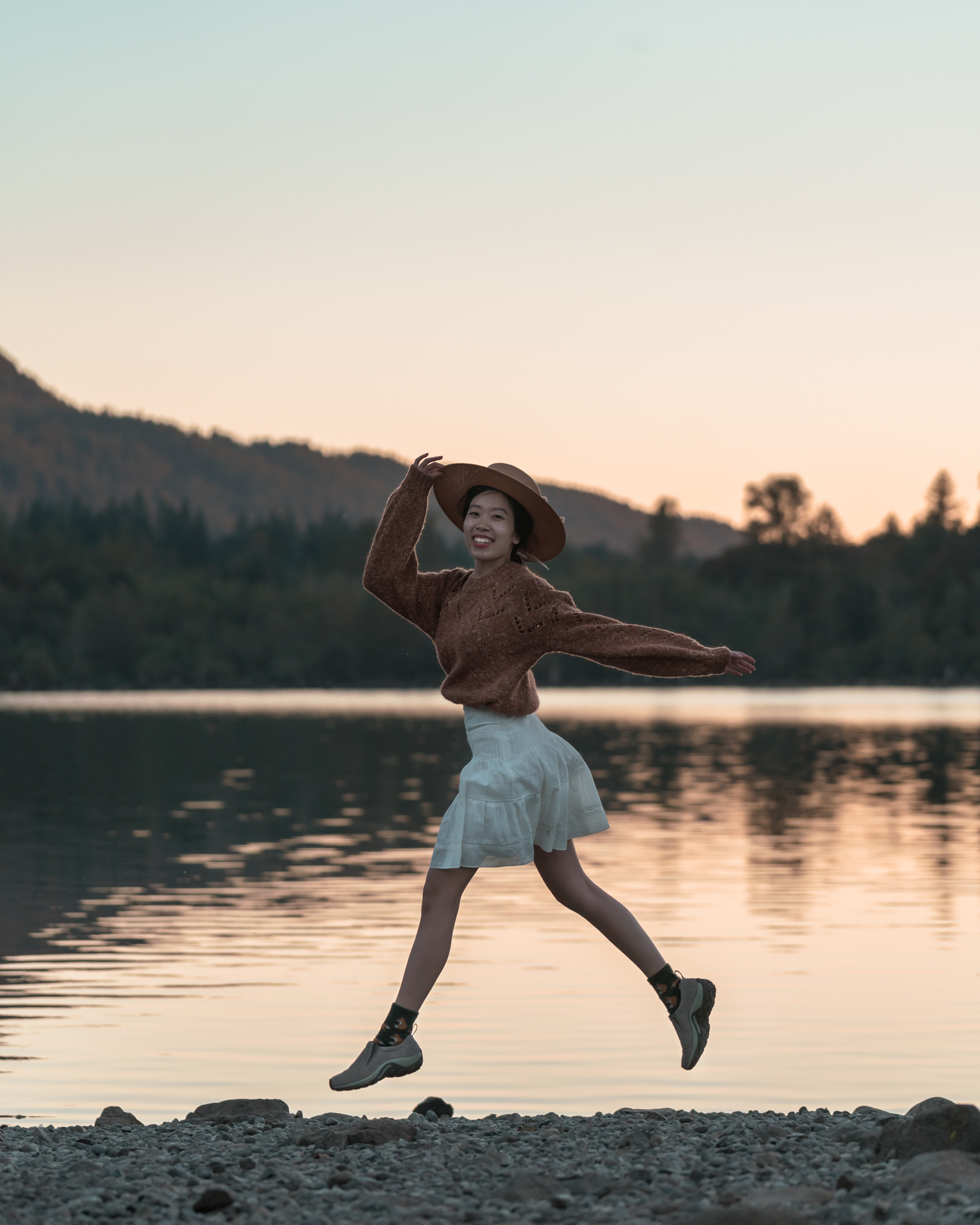 Girl leaping in the air at sunset in front of rattlesnake lake