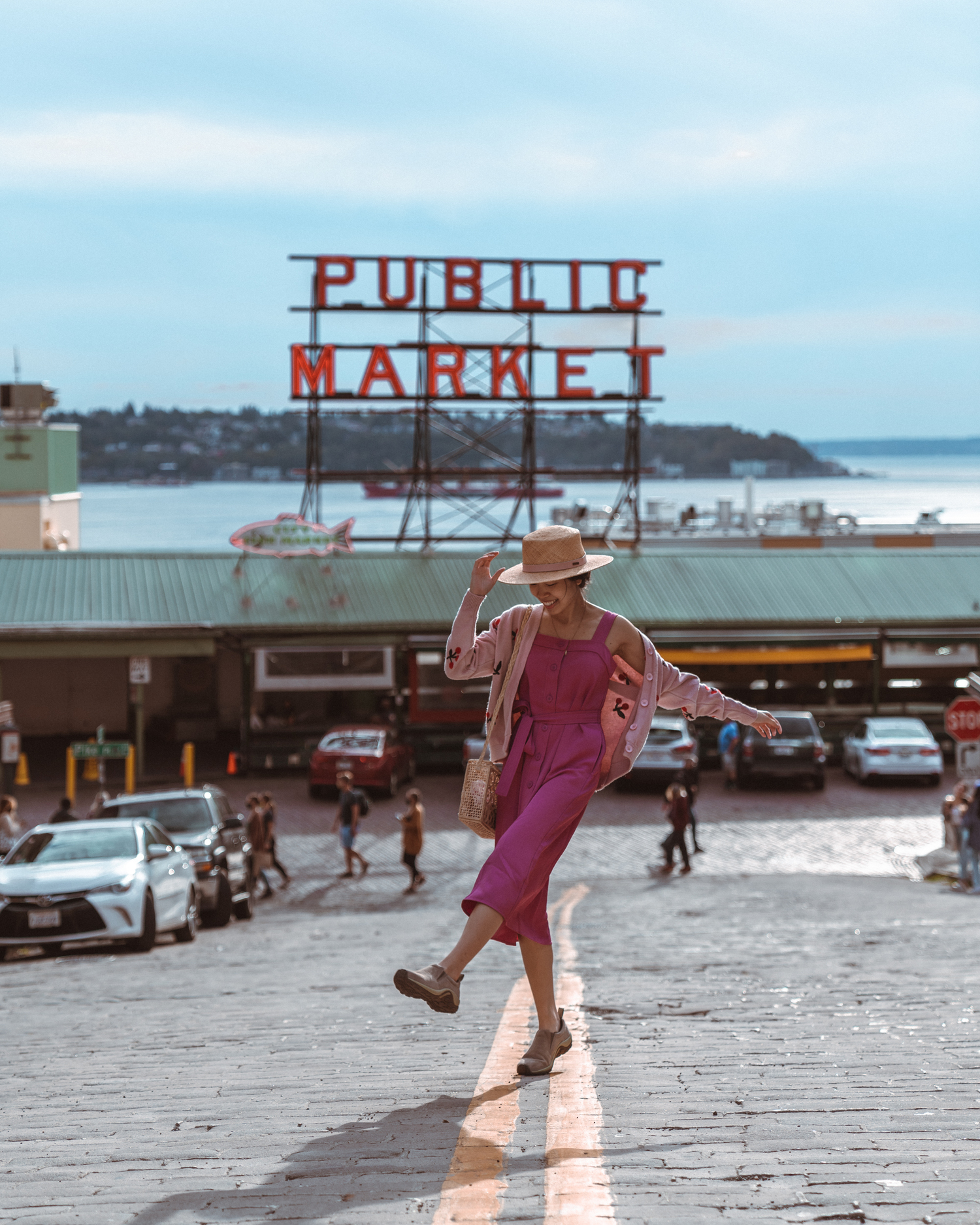 Girl in front of Public Market sign in middle of road at Pike Place Market, Seattle