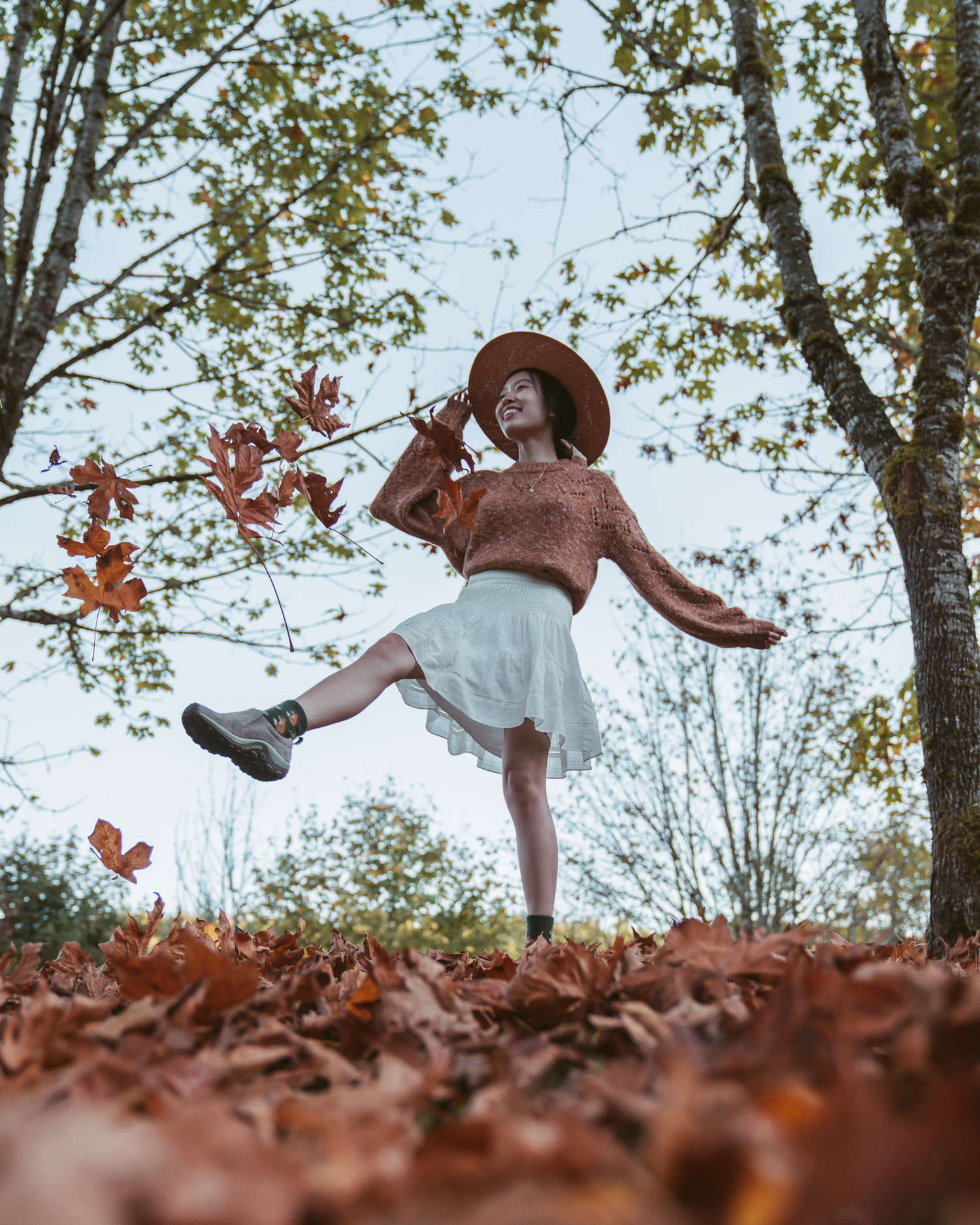 Girl smiling and kicking fall leaves into the air