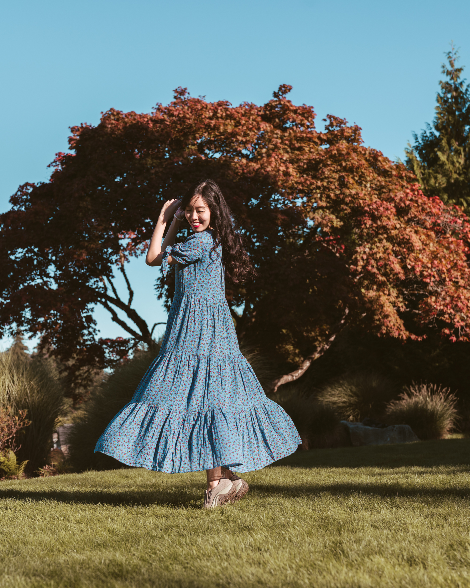 Girl twirling in blue dress in front of autumnal tree