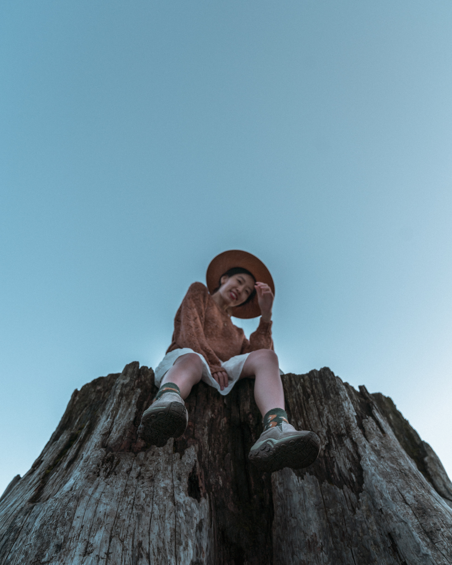Girl sitting on log with feet dangling