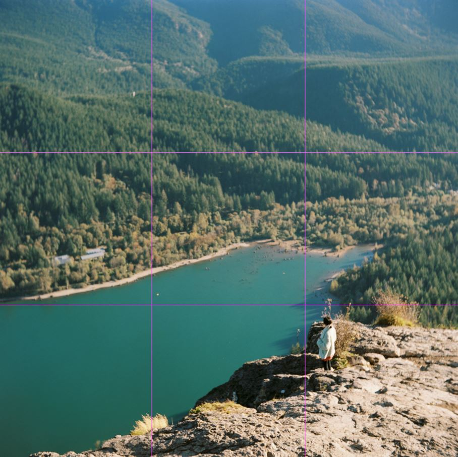 image of a girl standing on an overlook over a blue lake with rule of thirds