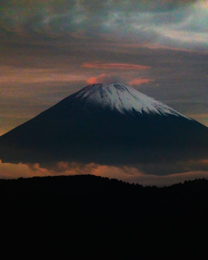 image of mount fuji rising above the clouds with sunset colors