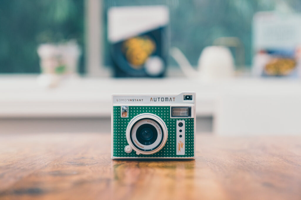image of a green instant film camera on a wooden table