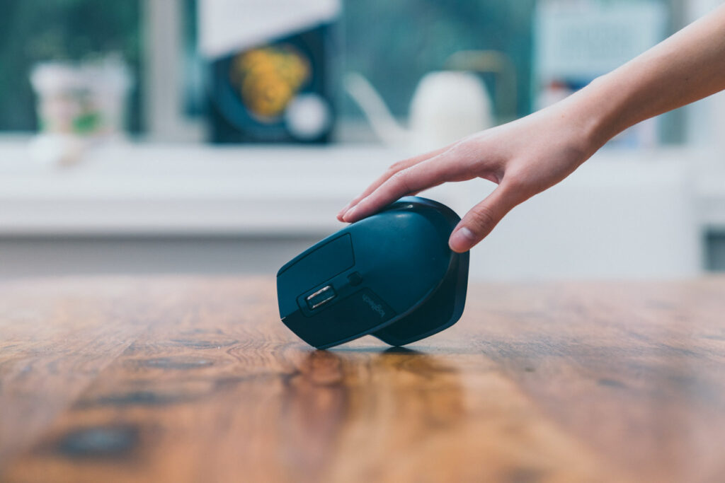 image of a black computer mouse being held on its side on wooden table