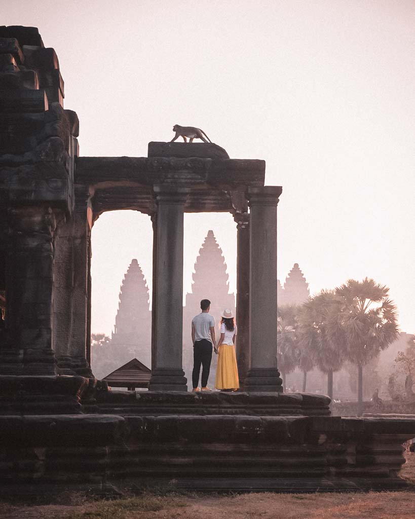 image of a couple on the steps of a ruin looking towards angkor wat. Monkey is above them making for an even more interesting image